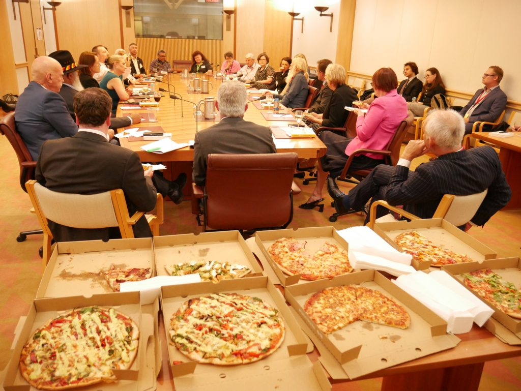 Pizza in open boxes in the foreground as polliticians listen to and talk to Bruce Pascoe and Anna Moulton from Magabala books about Dark Emu as part of the first Parliementary Book Club